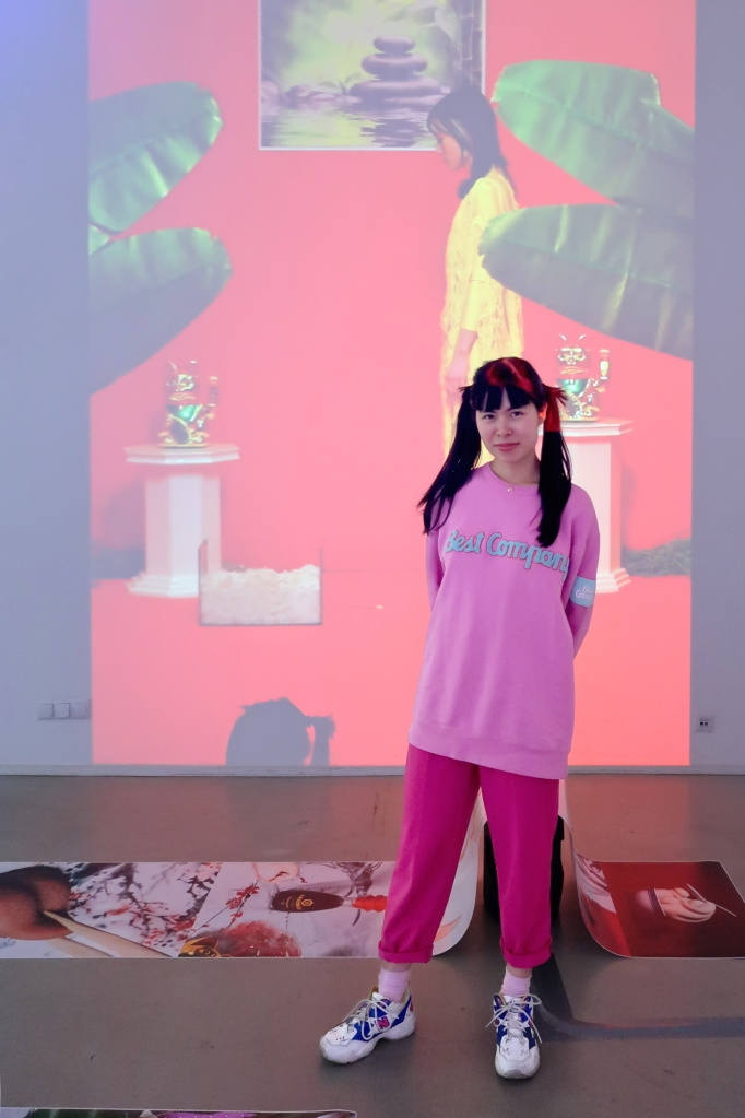 """Artist Hien Hoang in front of her exhibition featuring the performance video work """"Made in Rice"""" and """"Asia Bistro"""" in Frappant Gallery Hamburg, 2021"""